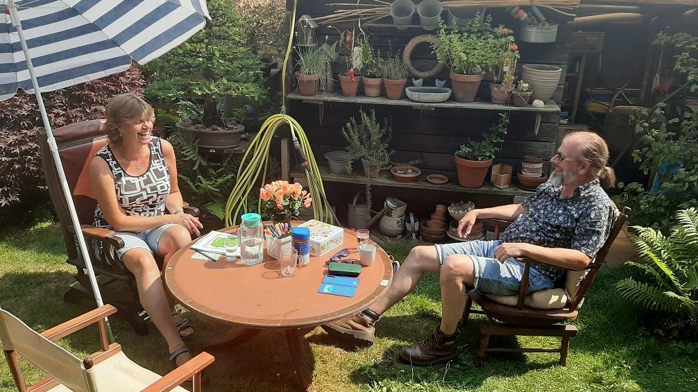 Franka Voortwist en Willem Cammel zitten op 2 schommelstoelen aan een lage ronde antieke tafel in de tuin van Franka. Er staat nog een derde stoel maar die is leeg. Ze zitten voor een wand met allemaal potjes met plantjes en kruiden erin. Op tafel staat een oranje gekleurd bloemetje in een bloemenpot. Op tafel staat ook een karaf met water en 2 glazen, er liggen wat spulletjes, koffie in mokken, een koektrommel, een pot met gekleurde viltstiften en een boek over de Matrix-methode.